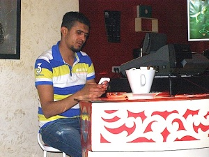 Night manager Hichem checks his messages while presiding over the cash register.